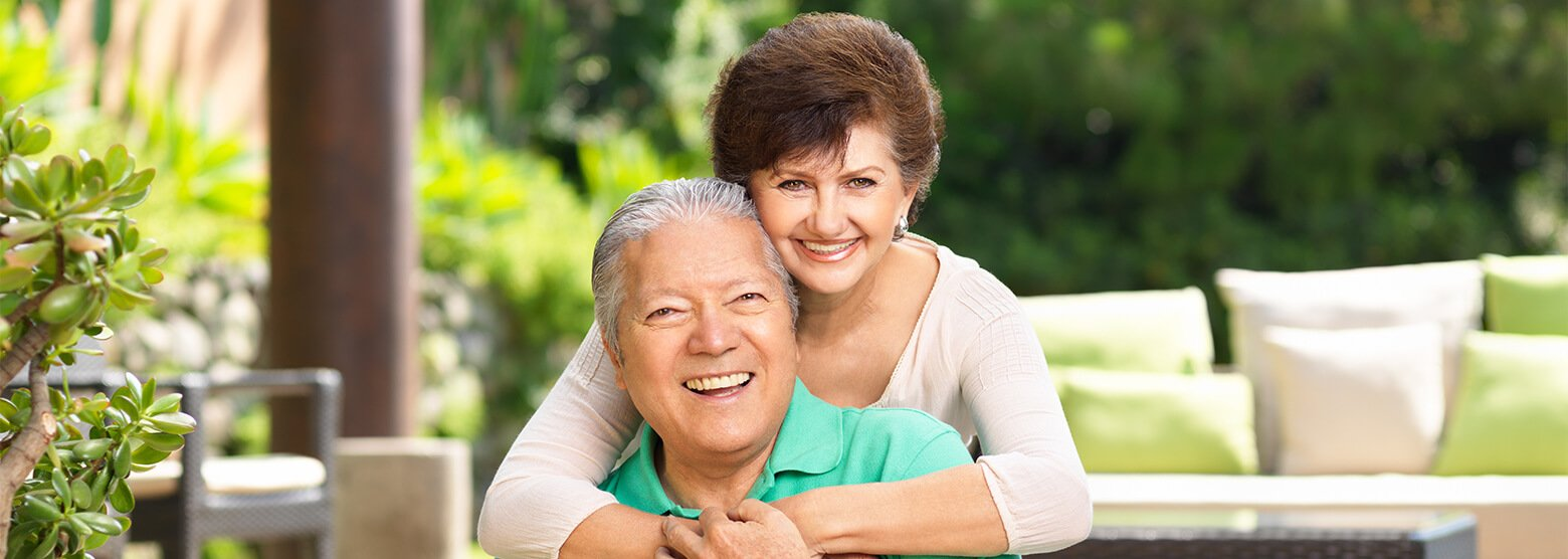 Older couple smiling while seated outside