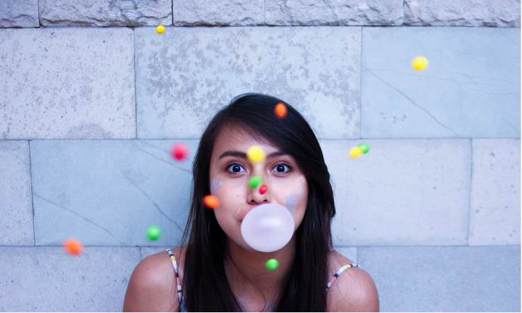 girl blowing a gum bubble with colored balls floating around her head